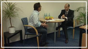 Szene aus dem Trainingsvideo zu Feedback im Business: Chef und Mitarbeiter im Gespräch über den Messeauftritt.