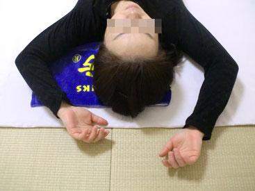 肩こり、首の痛み、頭痛の原因がわかるしんそう療方の手のバンザイ検査をしている写真です。
