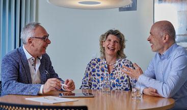Rainer Mayer bei der Anlageberatung am Besprechungstisch mit Laptop