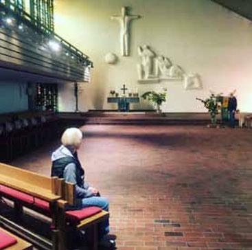 Frau sitzt allein in Kirche und schaut auf freie Fläche