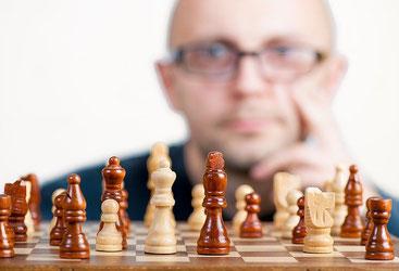 Mann mit Brille schaut auf Schachbrett