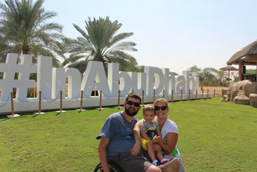 Young couple with child on grassy area in front of a sign that reads #InAbuDhabi