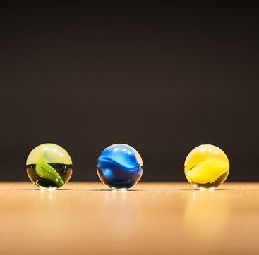 drei Murmeln in unterschiedlichen Farben