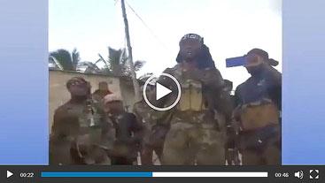 Gruppo di jihadisti davanti alla caserma della polizia di Quissanga con la bandiera nera dello Stato islamico