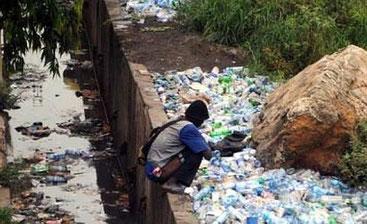 Un giovane nigeriano, circondato da rifiuti, scarica il proprio intestino in un corso d'acqua. Questa immagine è tutt'altro che rara nel grande Paese africano