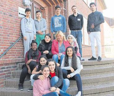 Die Schüler der DAZ-Klasse, hier mit Lehrerin Beate Kehr und Schulassistent Christoph Schlienger, erzählen in einer Bilderausstellung aus ihren Herkunftsländern.