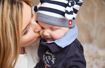 Junge Mutter, die ihr kleines Kind auf die Wange küsst