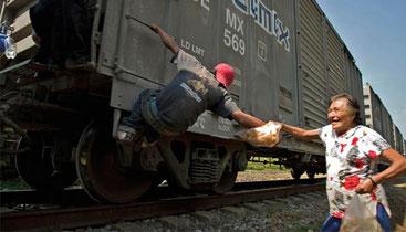 Una integrant de Las Patrones donant menjar a un immigrant dalt d'un tren en marxa