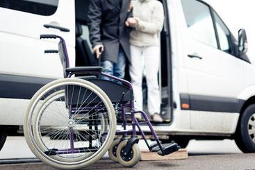Ein Rollstuhl steht vor dem Transportfahrzeug