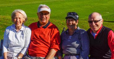 Zwei ältere Frauen und zwei ältere Männer sitzen auf einer Bank im Grünen.