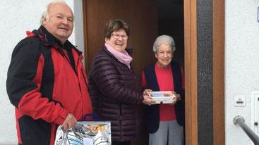 Eine Helferin und ein Helfer bringen die Mahlzeiten an die Haustür