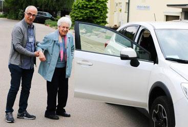 Ein Fahrer hilft einer älteren Frau beim Einsteigen