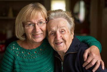 Eine jüngere Frau hält eine ältere Frau im Arm