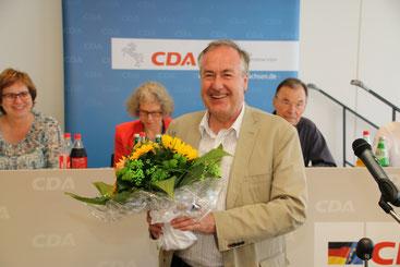 Von Vorne: Dr. Max Matthiesen freut sich nach seiner Widerwahl für zwei Jahre als Vorsitzender, dahiner rechts Tagungspräsident Wolfgang Peter Paul und Präsidiumsmitglied Christine Piefke.
