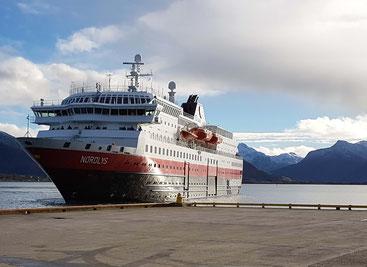 """Das Hurtigruten-Schiff """"Nordlys"""" kurz vor dem Anlegen im Hafen von Sortland auf den Lofoten. Im Hintergrund schneebedeckte Gipfel."""