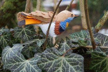 Kleiner in Handarbeit aus Filz hergestellter , dreidimensionaler Vogel , dem Blaukehlchen nachempfunden und in freier Natur fotografiert.