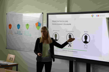 Studentin steht in Seminar-Raum vor Smart-Screen