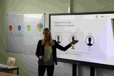 Studentin steht in Seminar-Raum vor Smart-Screen