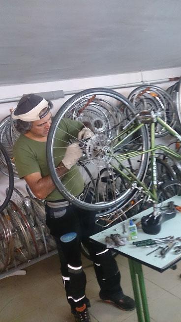 Recep bei der Fahrradreparatur, im Hintergrund sieht man viele ausgebaute Ersatzteile