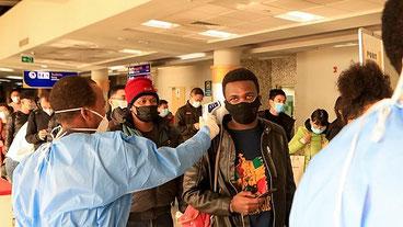 Gli operatori sanitari kenioti controllano i passeggeri dopo il loro arrivo dalla Cina, all'aeroporto internazionale Jomo Kenyatta di Nairobi