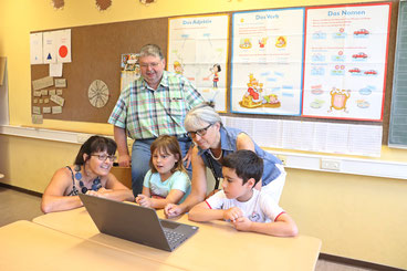 Das Förderteam Manuela Sieber (links) und Anja Opelt (2.v.r.) zeigen zwei Kindern sowie Hanno Steindorf, dem Vorsitzenden des Förderkreises, eine spannende Lernaufgabe am neuen Laptop.