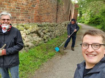 Robert Drews (r.) säubert mit Mitgliedern und Vorstandskollegen den Grünstreifen entlang der Stadtmauer.