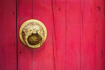 Goldener Türknauf auf rotem Holz