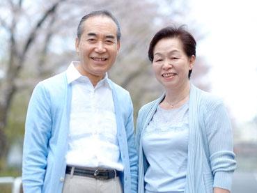 老夫婦が仲良く微笑んでいる写真。