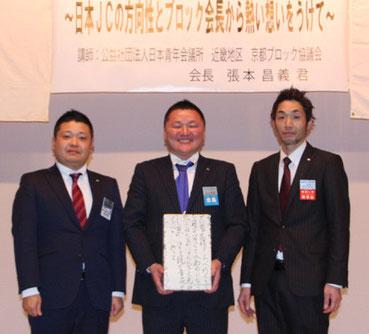 記念品贈呈後、記念撮影する(左から)上田理事長、張本会長、出口理事長
