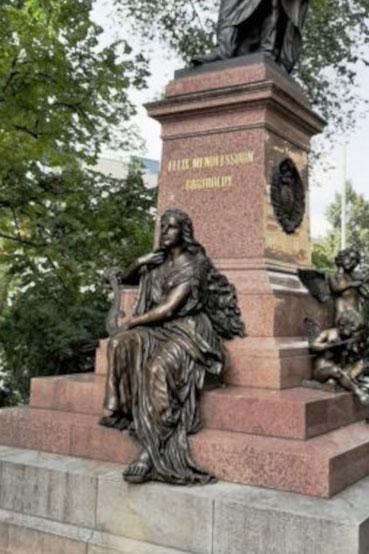 Dieses Bild zeigt die Statue einer Frau, die Harfe spielt. Es geht um das Thema Harmonie in der Musik und in zwischenmenschlichen Beziehungen.