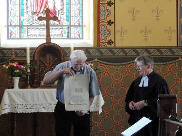 Pfarrer Oehlmann überreicht eine alte Bauzeichnung an Malermeister Klaus Dieter Kuthe.