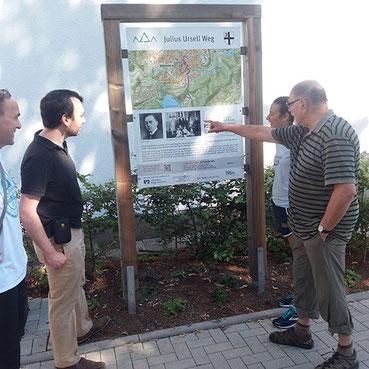 Vier Personen vor einem Wanderschild