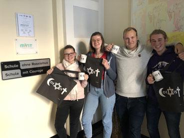 Vier junge Menschen mit CoeXisT-Artikeln