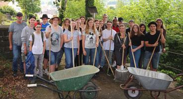 Viele Menschen mit Werkzeugen vor dem Jüdischen Friedhof in Attendorn)
