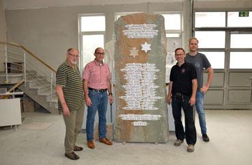 Vier Menschen an einer Gedenkstele