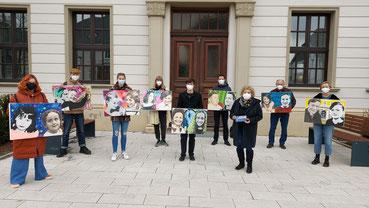 Neun Personen mit Kunstbildern in der Hand