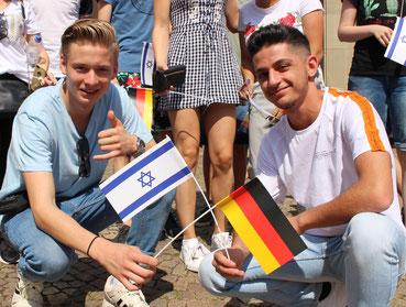 Zwei Jugendliche mit deutscher und israelischer Flagge