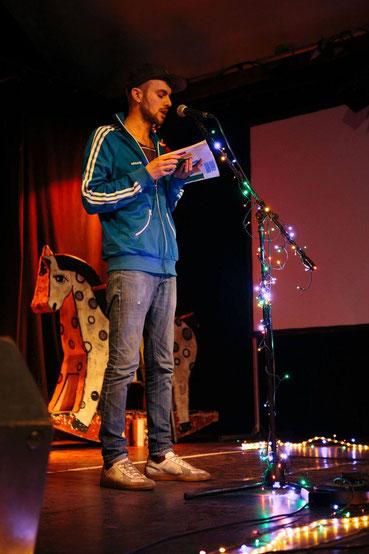 Ein Mann liest auf einer Bühne aus einem Buch vor und steht an einem Mikrofon