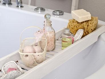 Naturkostmetikprodukte auf einem Brett über einer Badewanne