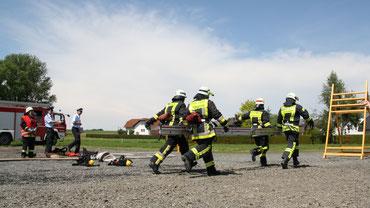 Vier Feuerwehrleute, welche mit einer Steckleiter laufen