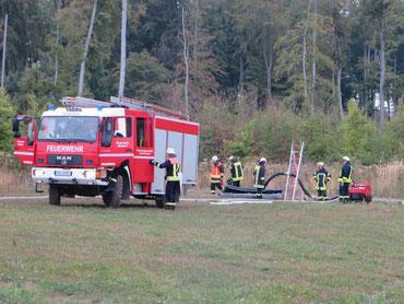 Löschfahrzeug, mehrere Feuerwehrleute beim Aufbau eines Wasserspeichers