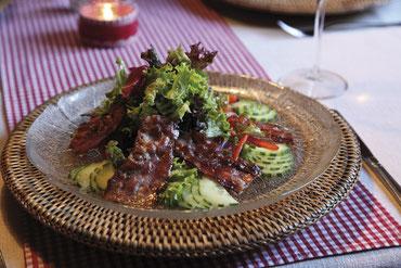 urchiger vorspeisensalat mit speckstreifen im restaurant alpencamping