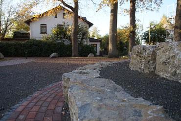 Eine Steintreppe mit zwei Stufen aus Muschelkalk-Natursteinen am Hüder Dorfplatz, im Hintergrund zu sehen sind die Eichen, unter denen die Bühne stellen soll.