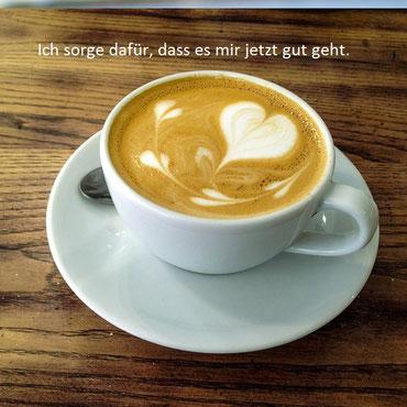 weiße Kaffee-Tasse mit Herzchen-Schaum auf Holztisch