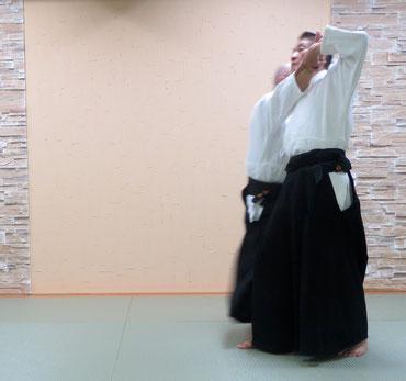 ④右足を軸として左足から左半身外入り身運動、送り足で右足の踵を左足内側(土踏まず側)に置く。その足先は受けの軸足を向く。右手は相対的に陽の陽、それを取る受けの手は昇氣で自身の側頸に。