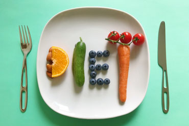 リンゴのかたちをしたフルーツバスケット。りんご、みかん、マスカットが載っている。