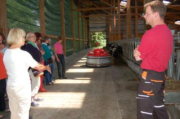"""Als """"wichtiger Mitarbeiter"""" auf dem Hof Ahrens präsentiert sich  beim Landfrauenbesuche der Roboter für das Anschieben der Gras- und Maissilage für die Kühe (v.r. Henning Ahrens, Henriette Ahrens,   Vorsitzende Helga Silber)"""