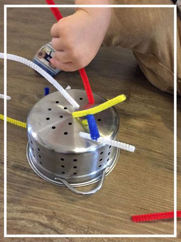 Steckspiel mit Pfeifenreinigern und einem Sieb - für Kleinkinder
