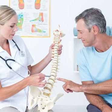 Ärztin erklärt an einem Rückenwirbelmodell Erkrankung