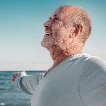 Älterer Mann steht mit geöffneten Armen am Meer